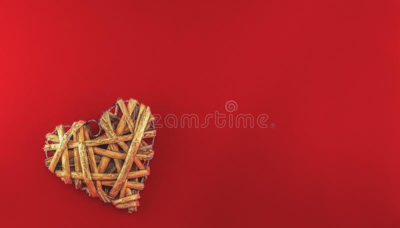 自然颜色的藤条心脏在红色背景的 免版税库存图片