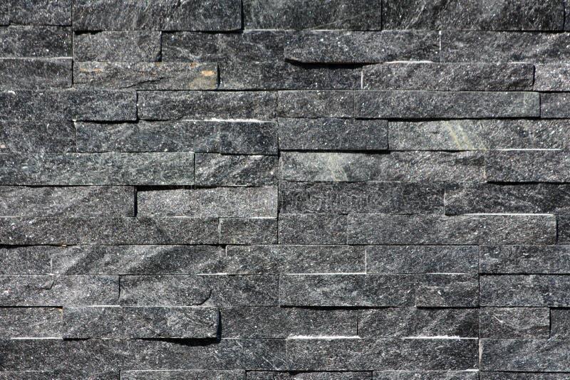 自然黑暗的石瓦片行在家庭房子墙壁纹理背景墙纸的 免版税图库摄影