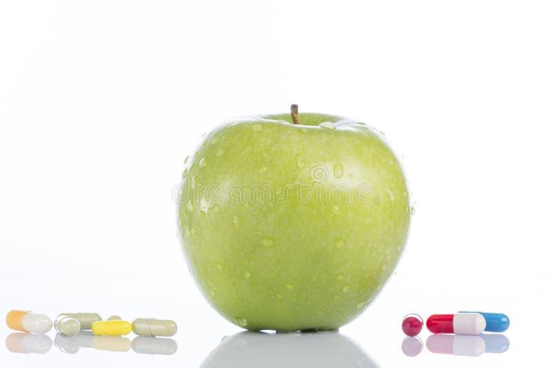 自然绿色苹果和各种各样的药片在白色 免版税库存图片