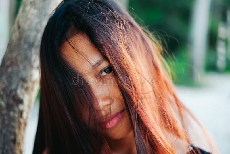自然画象美好年轻亚洲女孩微笑 杂乱女孩的头发 免版税库存照片