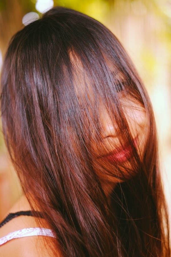 自然画象,微笑与在她的面孔的头发的亚裔女孩 当地亚洲秀丽 当地亚裔人民 免版税库存照片