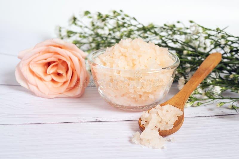 自然skincare概念 与桃红色玫瑰色盐温泉的有机化妆用品在玻璃碗和木匙子用桃红色玫瑰装饰 免版税库存照片