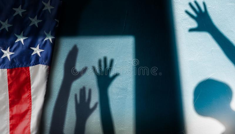 自由、表示和表决在美国概念 Rasing手的阴影从遮蔽在墙壁上的变化人的 图库摄影