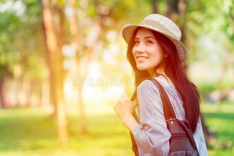 自由和发现概念:走在公园的偶然逗人喜爱的聪明的亚裔妇女 免版税库存图片