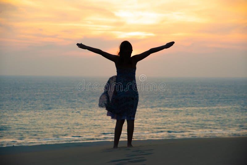 自由和愉快的女孩剪影海滩的 库存图片
