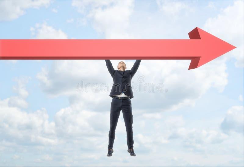 自由地垂悬在巨型红色箭头的商人 免版税库存照片