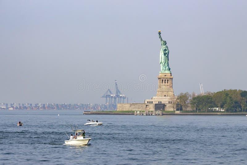 自由女神像有在背景中新泽西,纽约,美国的港 免版税图库摄影