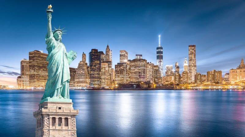 自由女神像有更低的曼哈顿背景在晚上,纽约地标  免版税库存图片