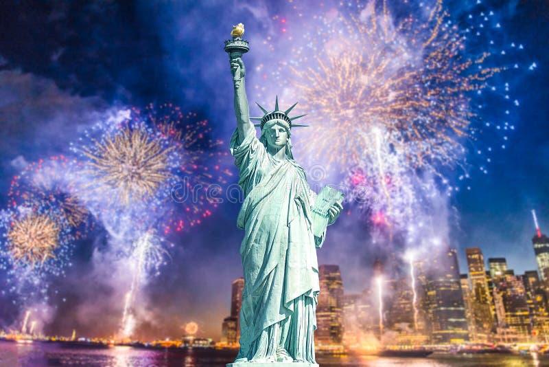 自由女神像有都市风景被弄脏的背景与美丽的烟花在晚上,曼哈顿,纽约的 免版税库存图片