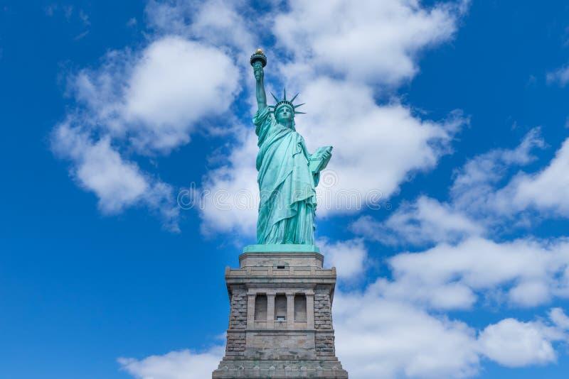 自由女神像的正面图与天空蔚蓝和云彩在一好日子,纽约,美国的 免版税库存照片