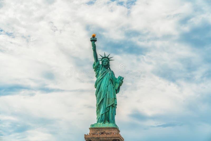 自由女神像,反对多云天空蔚蓝的纽约 免版税库存照片