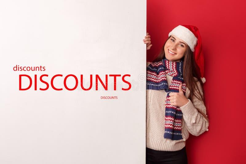 自由式 在与看照相机的白板赞许的红色隔绝的年轻女人佩带的围巾和圣诞老人帽子身分 免版税库存图片