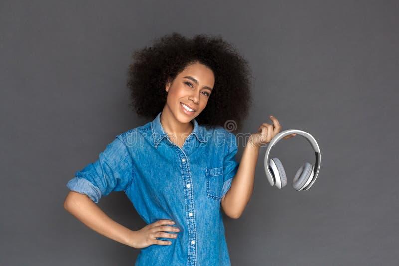 自由式 混血儿在与耳机微笑的灰色隔绝的妇女身分暴牙 免版税库存照片