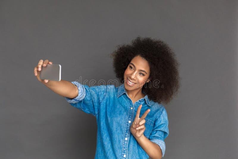 自由式 混血儿在显示和平姿态的智能手机的灰色采取的selfie隔绝的妇女身分快乐 免版税库存照片