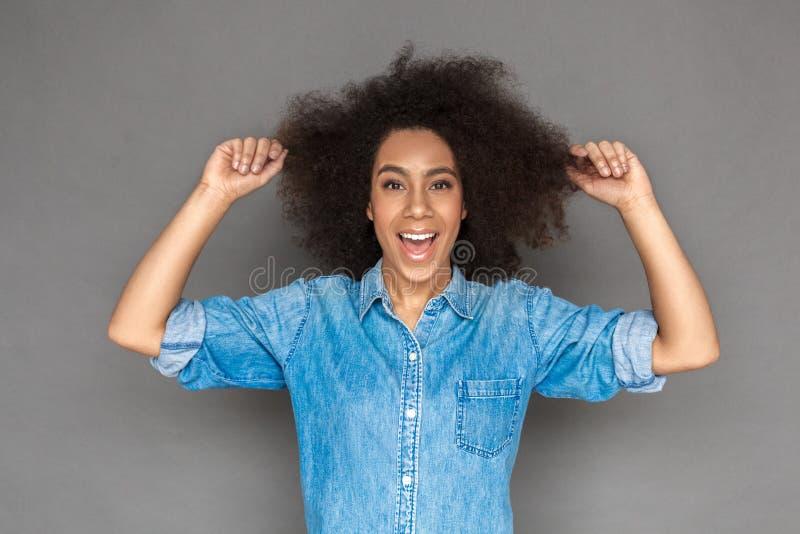 自由式 混血儿在灰色举行的头发隔绝的妇女身分看嬉戏的照相机 图库摄影