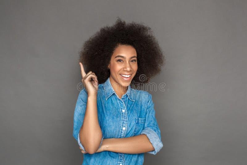 自由式 混血儿在灰色指向隔绝的妇女身分创造性想法微笑愉快 免版税库存图片