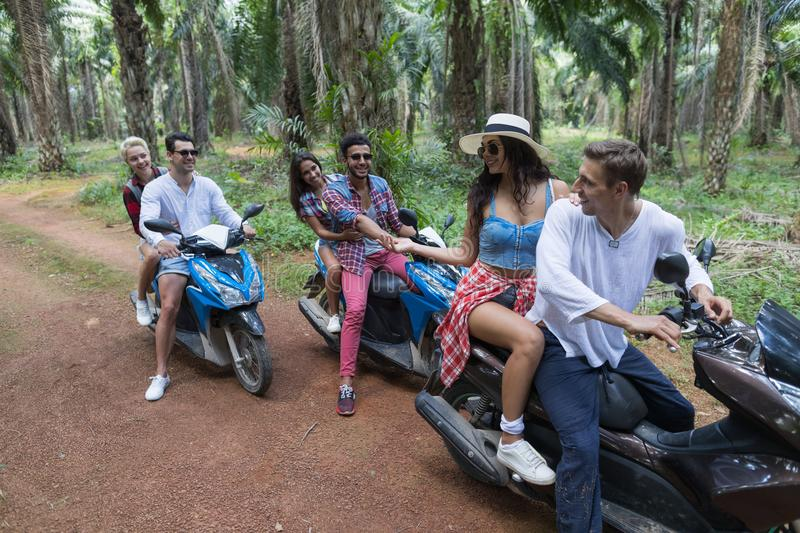 自由快乐的人通信坐小组年轻朋友旅行的滑行车自行车一起享受假期 免版税图库摄影