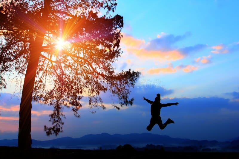 自由概念、剪影妇女愉快地跳跃在假日的,与冒险的年轻少年休闲和野营 图库摄影