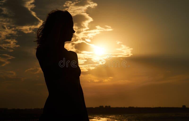 自由的妇女剪影日落的在海滩 免版税图库摄影