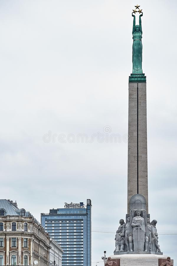 自由纪念碑里加 拿着象征拉脱维亚的三个地区的三个金星的妇女 图库摄影