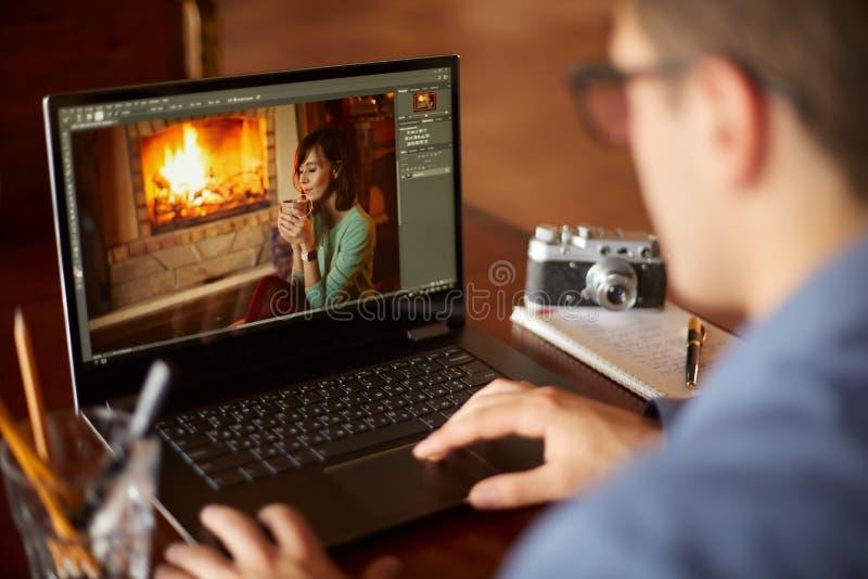 自由职业者工作在有照片的便携式计算机编辑sofware的retoucher人 摄影师或设计师在工作 图库摄影