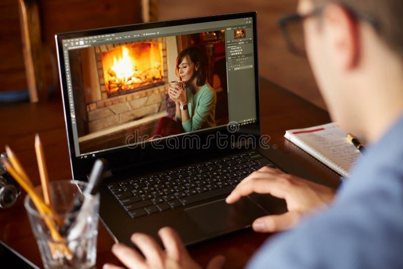 自由职业者工作在有照片的便携式计算机编辑sofware的retoucher人 摄影师或设计师在工作 免版税库存图片