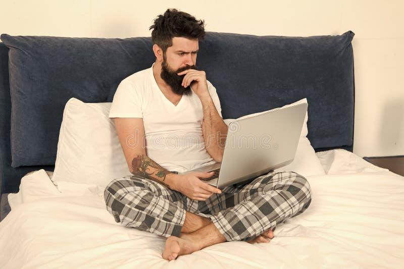 自由职业者的工作 逗留在床上和继续工作 自由职业者的好处 人冲浪的互联网或在网上工作 有胡子的行家 免版税图库摄影