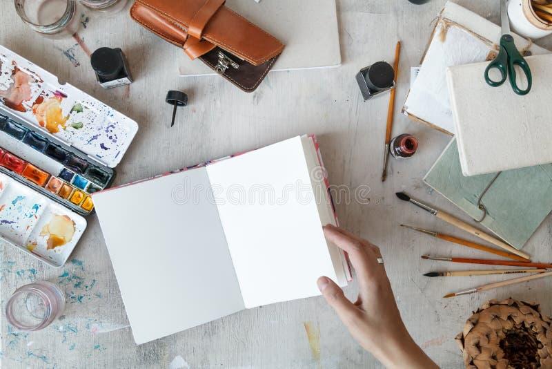 自由职业者的艺术家工作场所有被打开的写生簿顶视图 库存照片