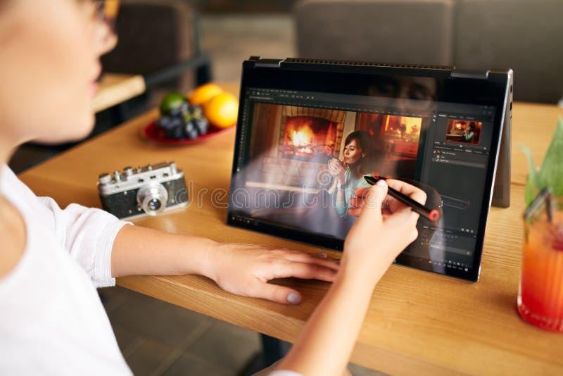 自由职业者研究有照片的敞篷车便携式计算机编辑软件的retoucher妇女使用铁笔 摄影师 免版税库存照片