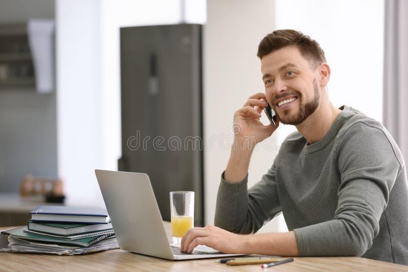 自由职业者谈话在电话,当使用膝上型计算机在家时 免版税库存照片
