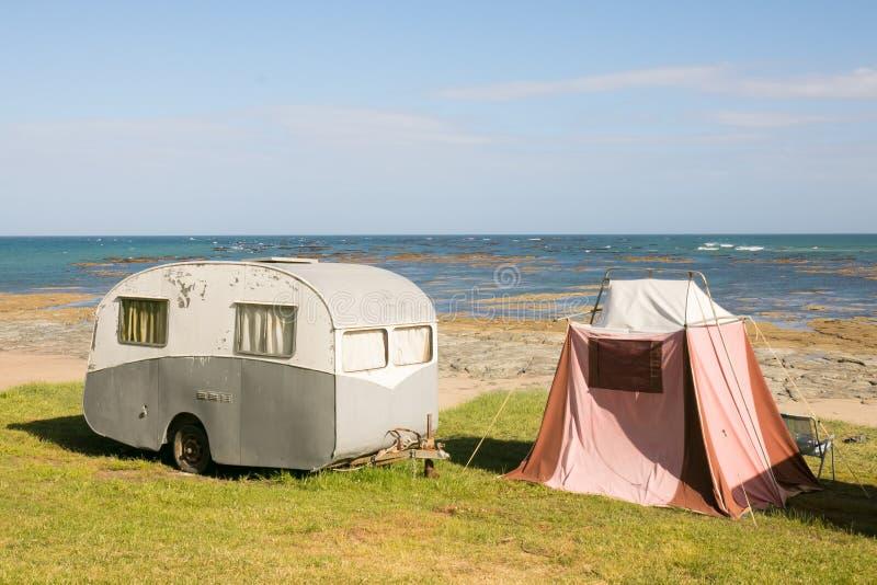 自由野营在葡萄酒有蓬卡车的和帐篷在东海岸靠岸,吉斯伯恩,北岛,新西兰 库存图片
