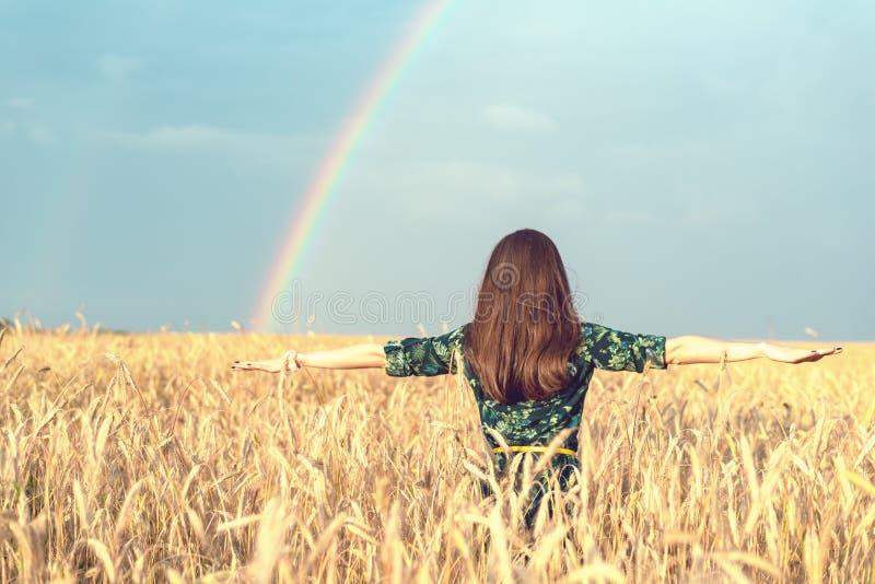 自由 愉快的微笑的妇女用在麦田的开放手与看在彩虹背景的天空的金黄小尖峰 库存照片