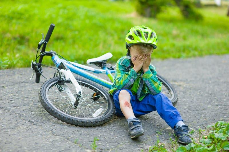 从自行车下落了的哭泣的孩子 免版税图库摄影