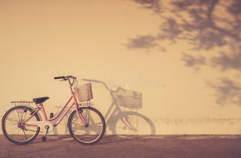 自行车停放了在墙壁和阴影旁边的早晨时间与a 免版税库存图片