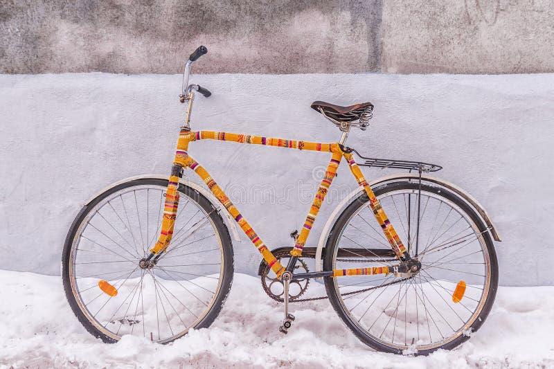 自行车在一条多雪的街道上装饰的被绝缘的被编织的服装 库存照片