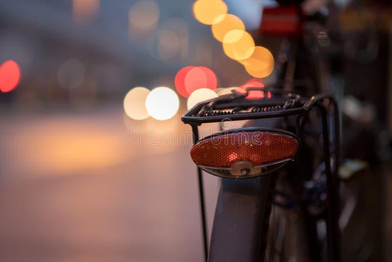 自行车在城市,黄昏:城市自行车的后方图片,被弄脏的背景 免版税库存图片