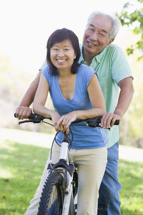 自行车夫妇成熟骑马 库存照片