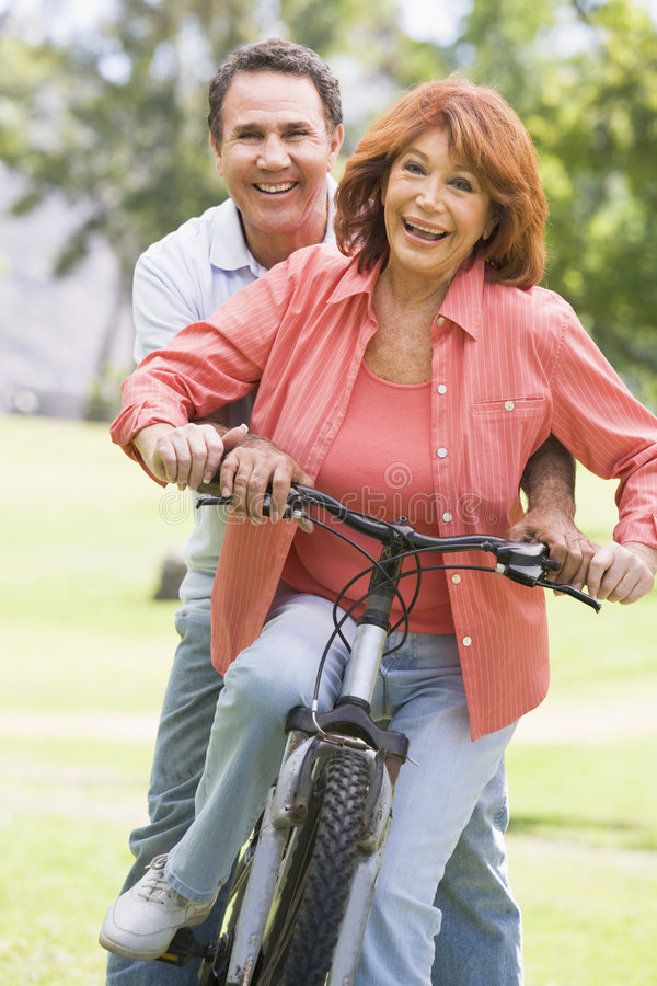 自行车夫妇成熟骑马 免版税库存照片