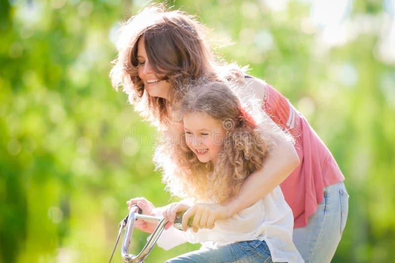 自行车女儿她的母亲年轻人 免版税库存图片