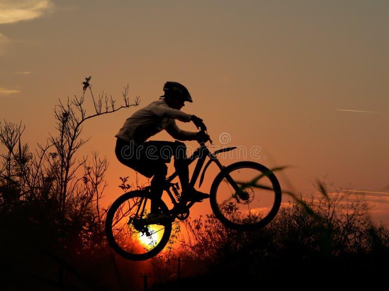自行车山竟赛者剪影 图库摄影