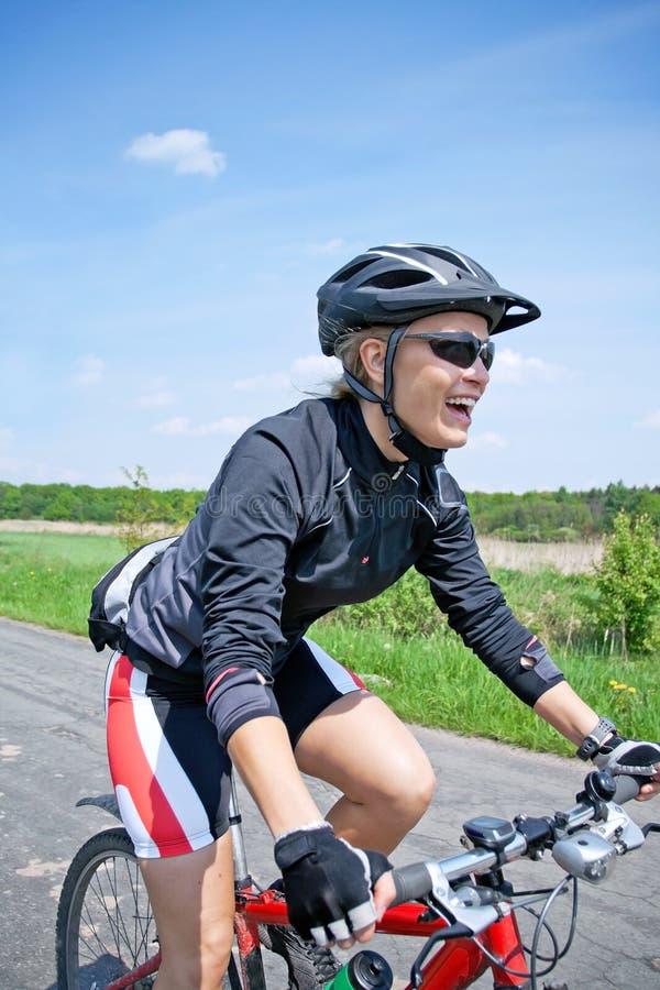 自行车日骑马夏天妇女 免版税库存图片