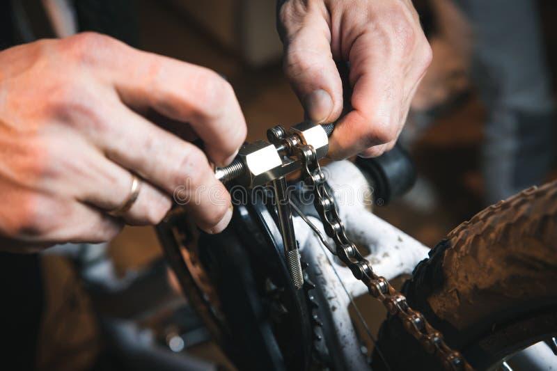 自行车服务:技工安装装配或调整的军人安装工自行车齿轮在轮子在车间 免版税库存图片