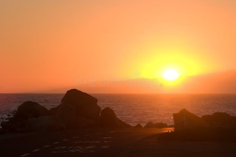 自行车海洋路径日落 免版税库存图片