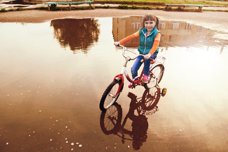 自行车的孩子通过一个水坑乘坐在秋天天 免版税库存照片
