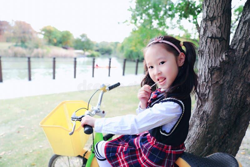 自行车的小女孩在公园ï ¼ ŒWith棒棒糖在手中 图库摄影