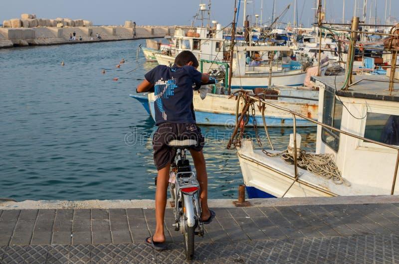 自行车的未定义孩子在老贾法角口岸的堤防 库存图片