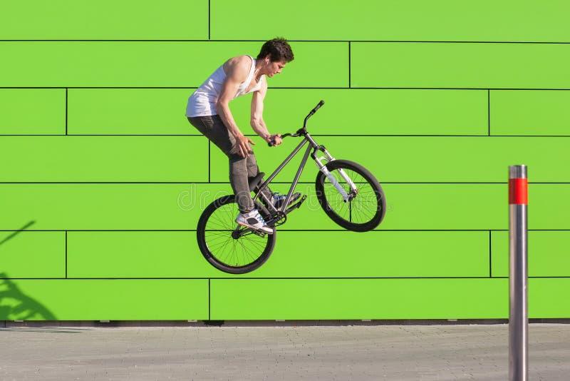 自行车的男孩做barspin欺骗在绿色墙壁背景 库存照片