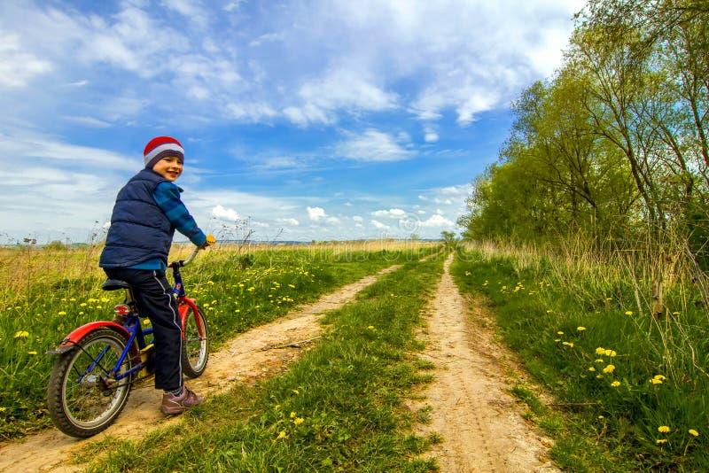 自行车的男孩在乡下公路晴朗的春日 免版税库存照片