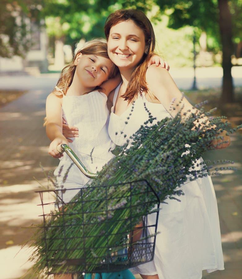 自行车的美丽和愉快的少妇有她的女儿的 图库摄影