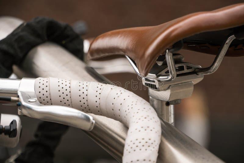自行车豪华细节 有皮革方向盘的停放的自行车在赛跑自行车和布朗皮革自行车备鞍 库存图片